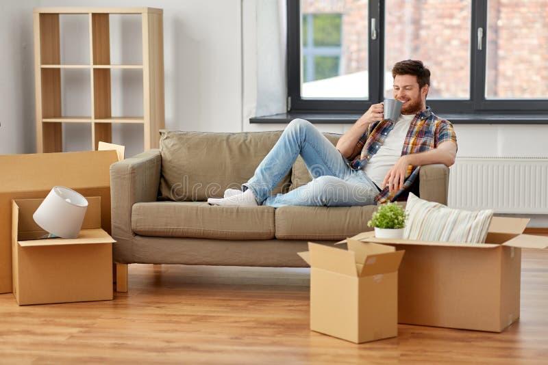 Man med askar och drickakaffe på det nya hemmet royaltyfri fotografi
