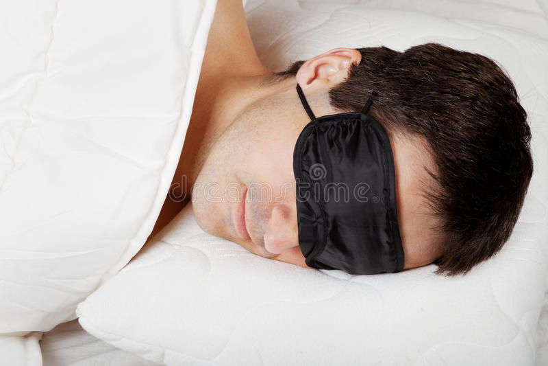 Man med att sova maskeringen som ligger i säng royaltyfri fotografi