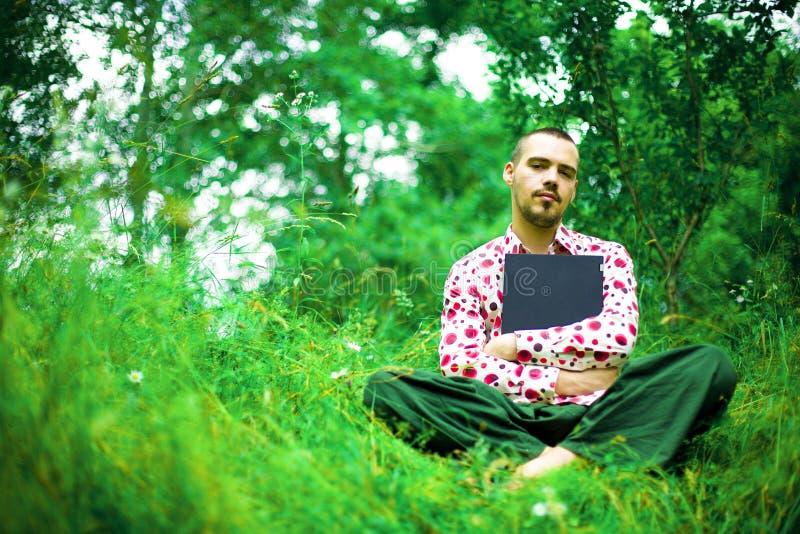 Man med bärbar dator i trädgård arkivfoto
