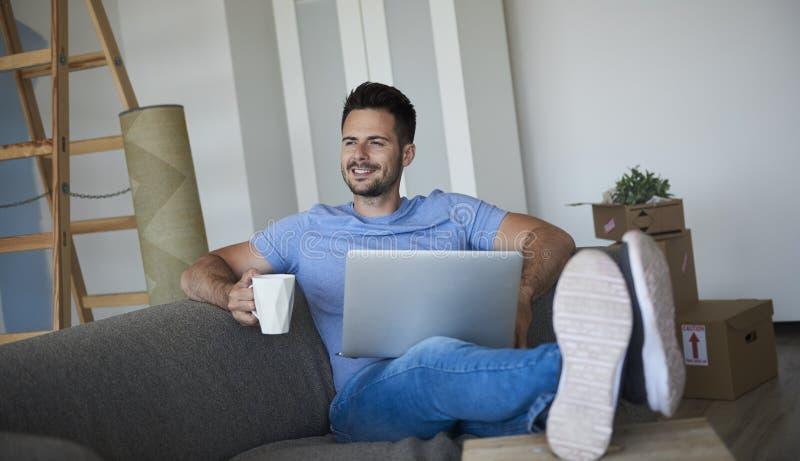 Man med bärbara datorn och kaffe som har avbrottet från rörande hus royaltyfria bilder