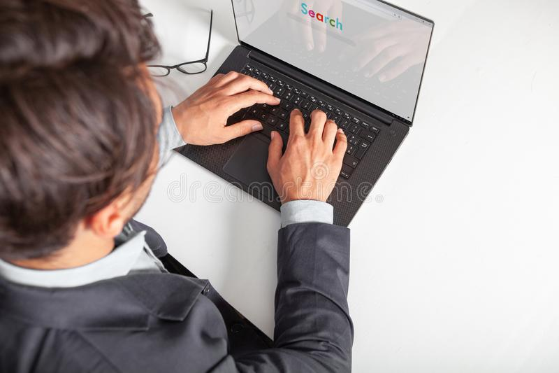 Man med bärbara datorn som skriver på tangentbordet som gör ett sökande med en sökandemotor arkivfoton