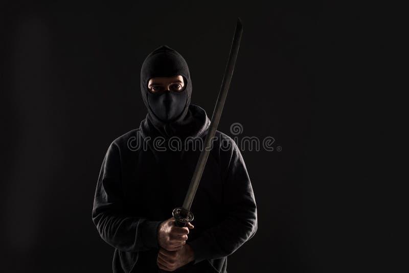 Man med balaclavaen och katanasvärdet på svart bakgrund arkivbild