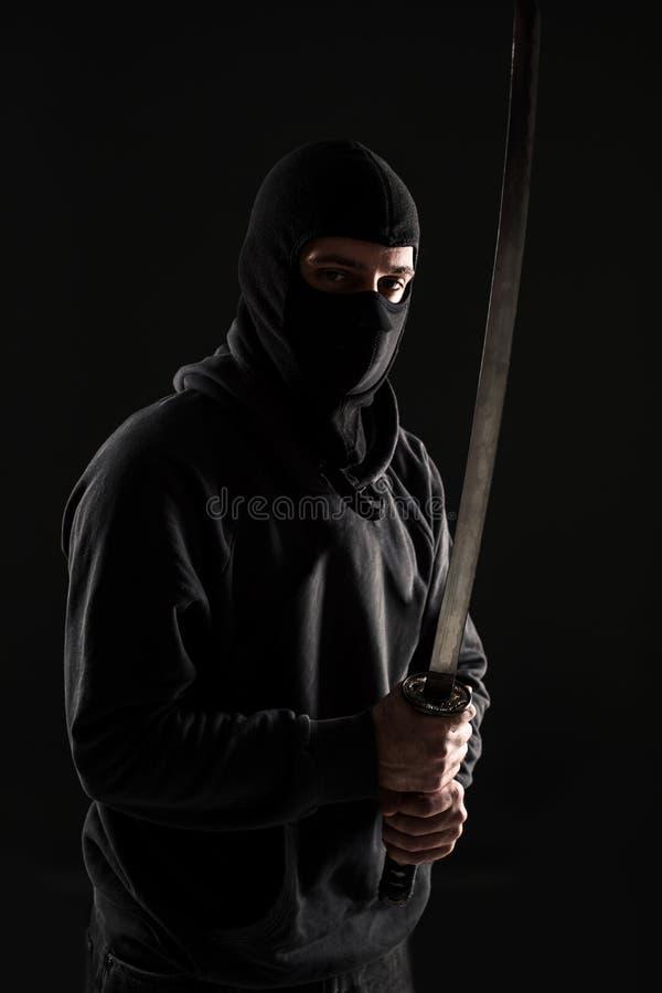 Man med balaclavaen och katanasvärdet på svart bakgrund arkivfoton