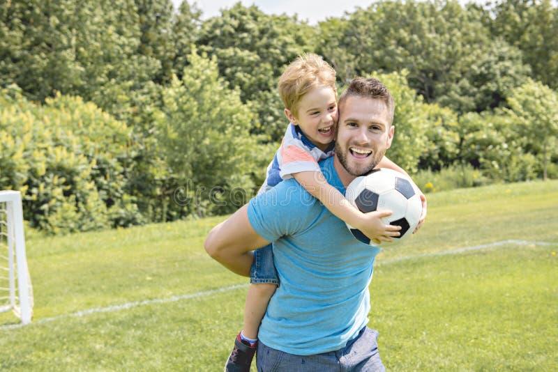 Man med barnet som spelar fotboll utanför på fält royaltyfria foton