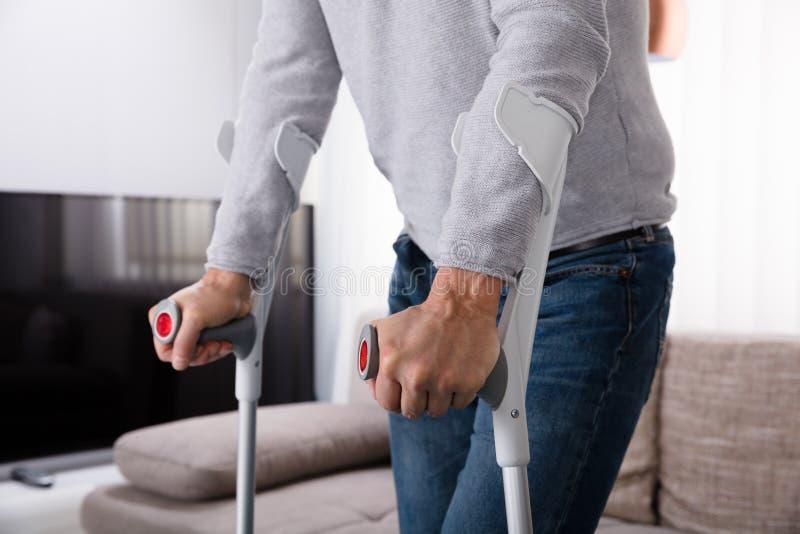 Man med benbrottet genom att använda kryckor arkivfoto