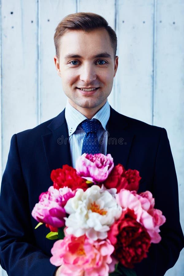 Man med blommor arkivbild