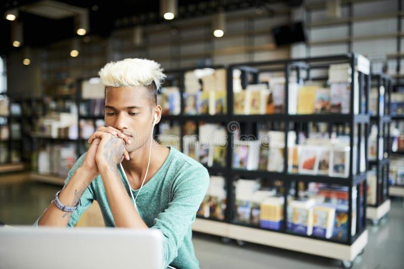 Man med blond mohawk som tänker om universitetforskning royaltyfri foto