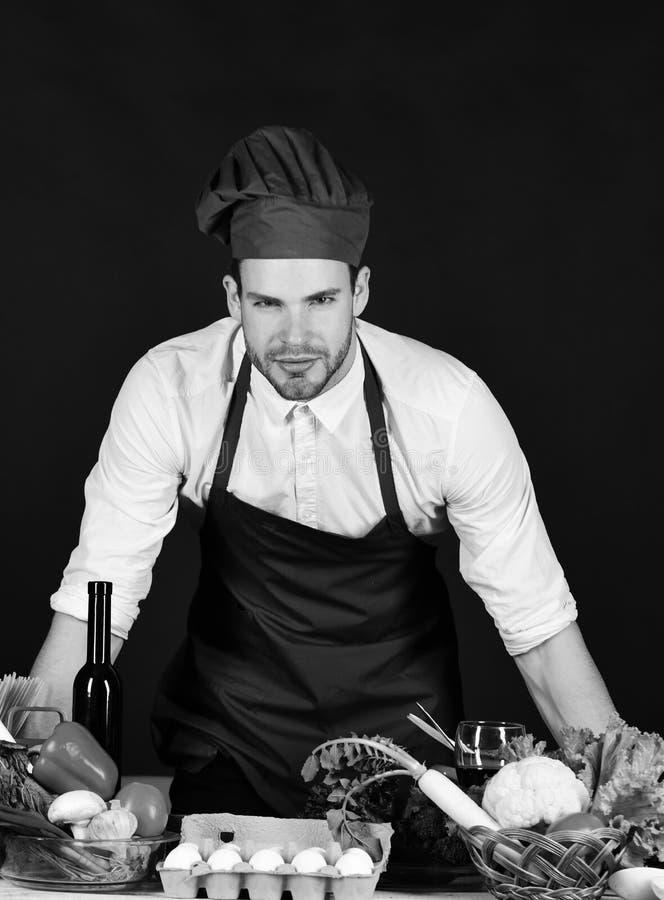 Man med borstet i den burgundy kocken eller kocklikformig royaltyfria foton