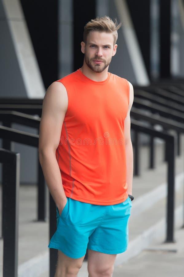Man med borstet på allvarlig framsida i sportiga kläder, stads- bakgrund Sportmodebegrepp Attraktiv grabb som uppsökas och royaltyfria foton
