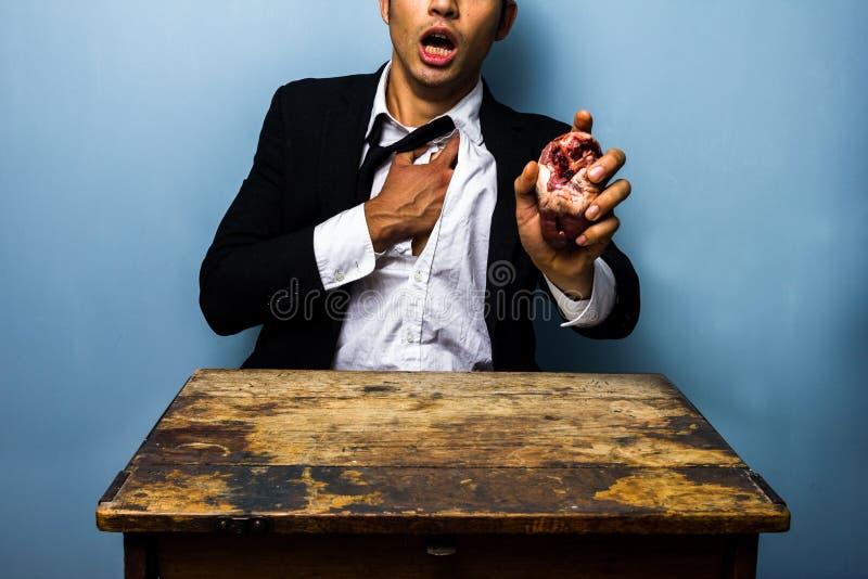 Man med bröstkorgplågor som rymmer en hjärta i hans hand fotografering för bildbyråer