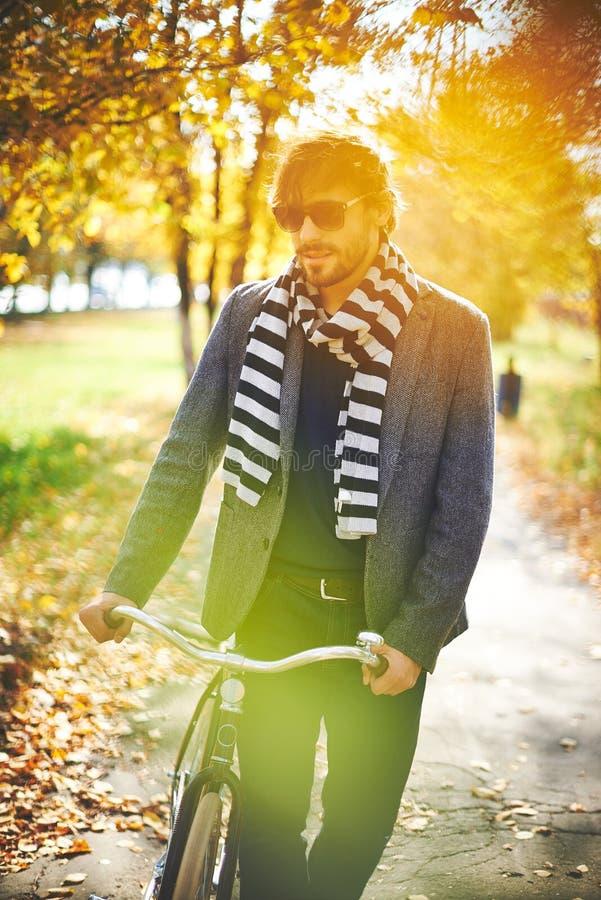 Man med cykeln arkivfoto