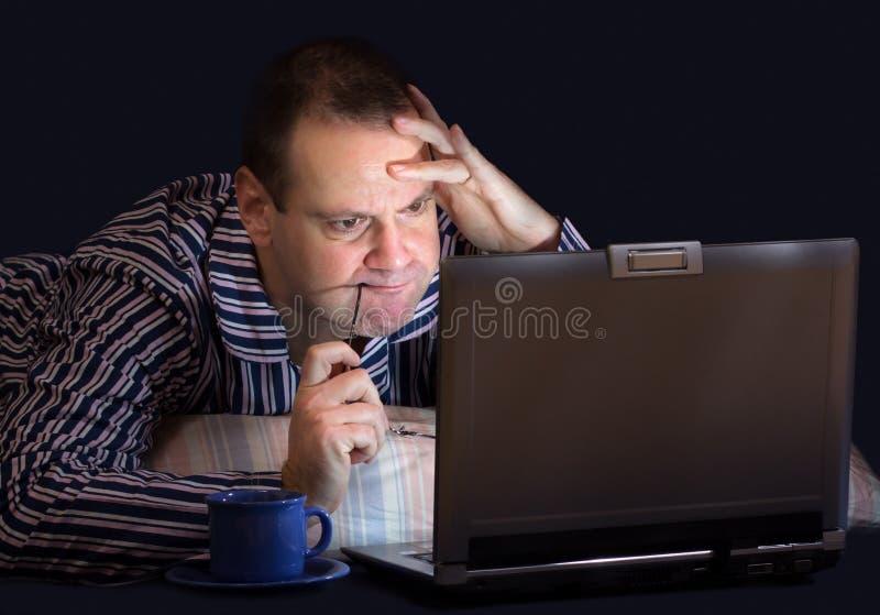 Man med datoren i säng arkivfoton