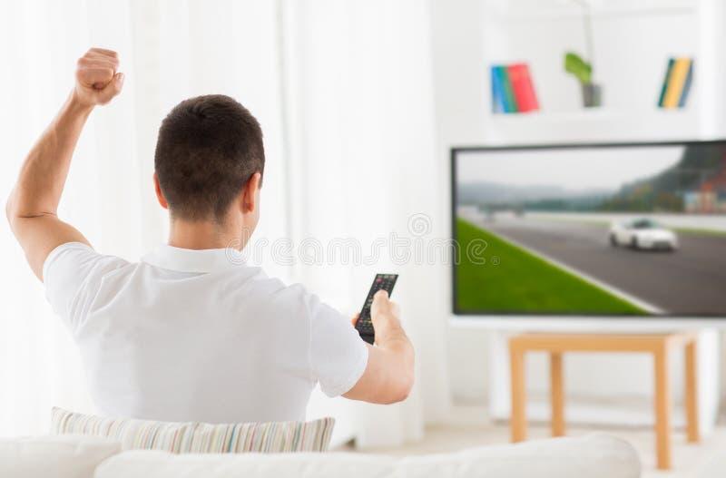 Man med den avlägsna hållande ögonen på motorsportsen på tv hemma royaltyfria foton