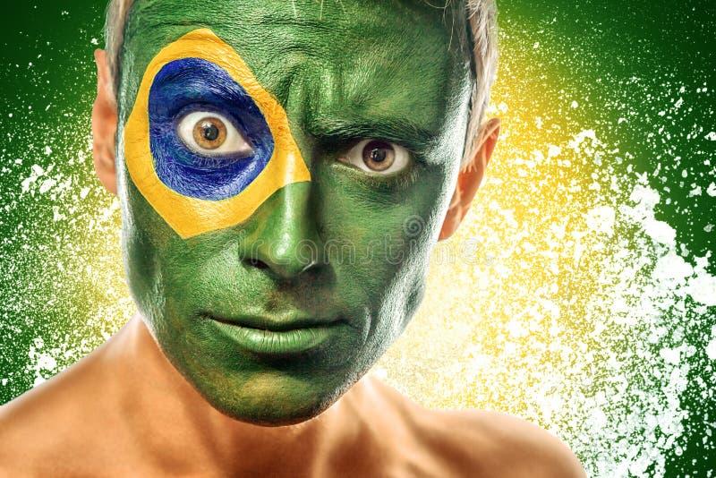 Man med den Brasilien flaggan som målas på framsida arkivfoto