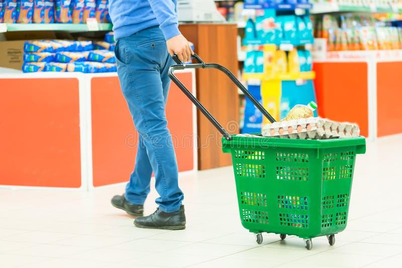 Man med den fulla shoppingvagnen i supermarket ben för bakgrundspåsebegrepp som shoppar den vita kvinnan Selektivt fokusera arkivfoto
