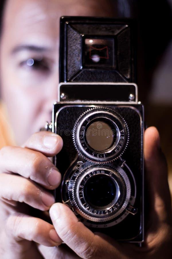 Man med den gamla tappningkameran i händer Fokus till manögon Det tappning stiliserade fotoet av manfotografen med gammal TLR kop royaltyfri bild