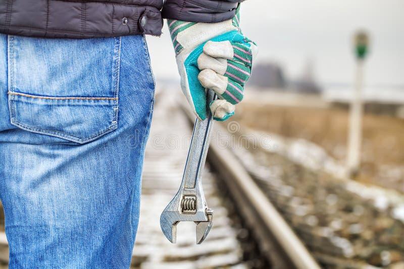 Man med den justerbara skiftnyckeln på järnvägen fotografering för bildbyråer