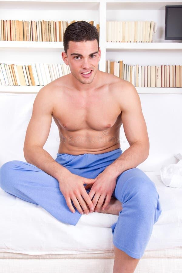 Man med den nakna torson i pyjamas som kopplar av på soffan arkivfoton