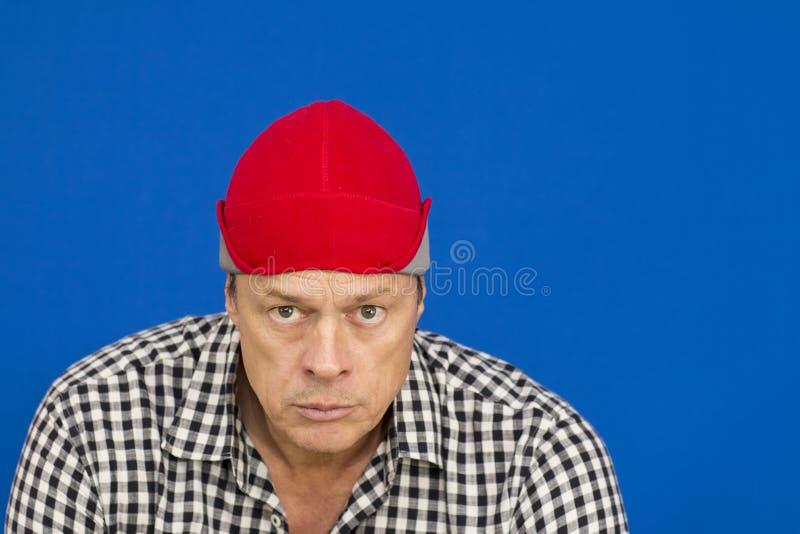 Man med den röda hatt- och plädskjortan royaltyfri foto