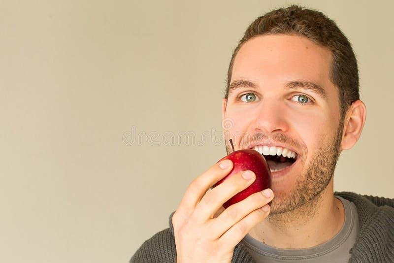 Man med den roliga framsidan som ser ett äpple royaltyfria foton