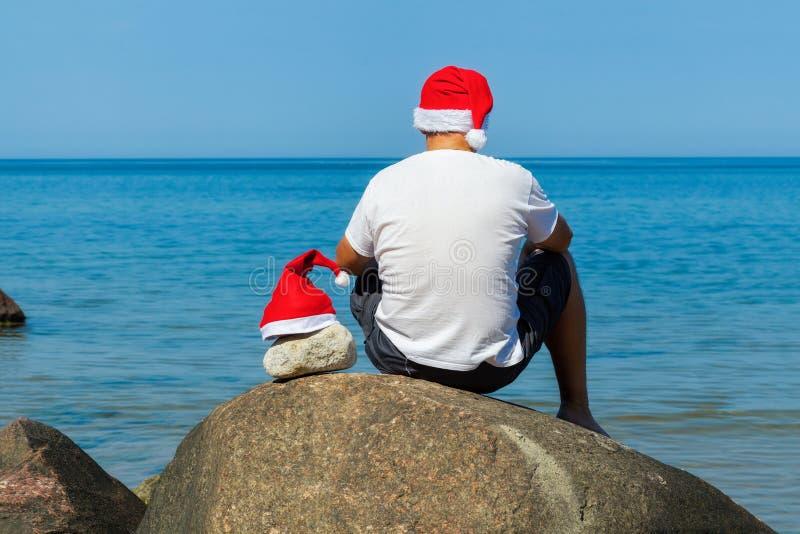 Man med den Santa Claus hatten som kopplar av nära havet i sommar royaltyfri foto