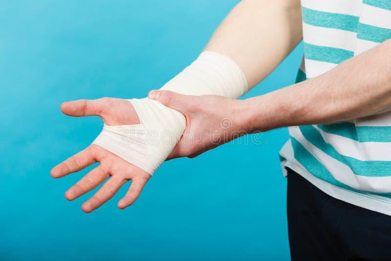 Man med den smärtsamma förband handen arkivfoto