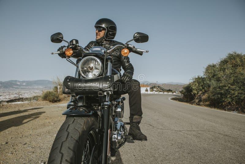 Man med den svarta hjälmen, omslaget och solglasögon som står på en klassisk amerikansk motorcykel arkivfoton