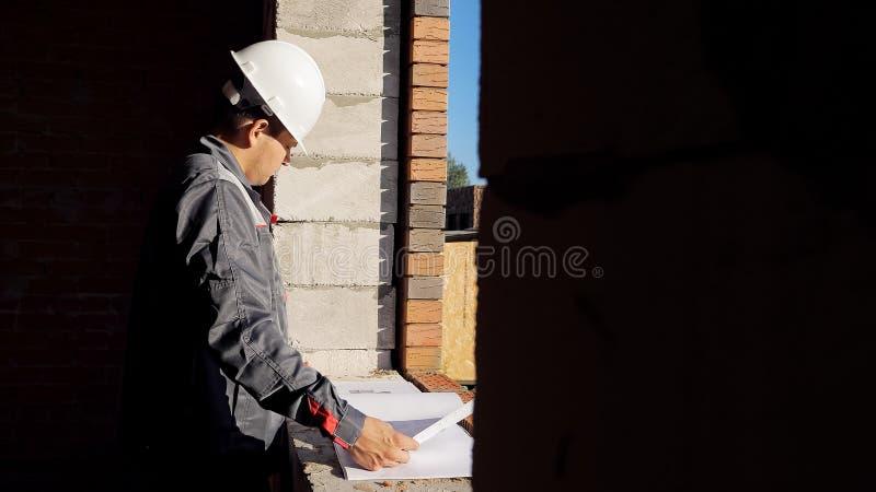 Man med det pappers- utkastet i byggnad under konstruktion fotografering för bildbyråer