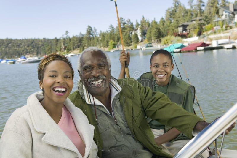 Man med dottern och sonsonen som tillsammans fiskar arkivfoton