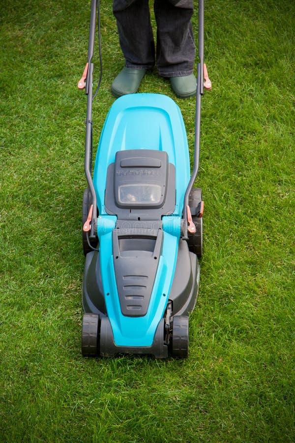 Man med en elektrisk gräsklippningsmaskin arkivbild