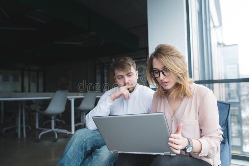 Man med en flicka som sitter i kontoret på soffan och ser bärbara datorn Kontorsarbetare vilar på soffan royaltyfria bilder
