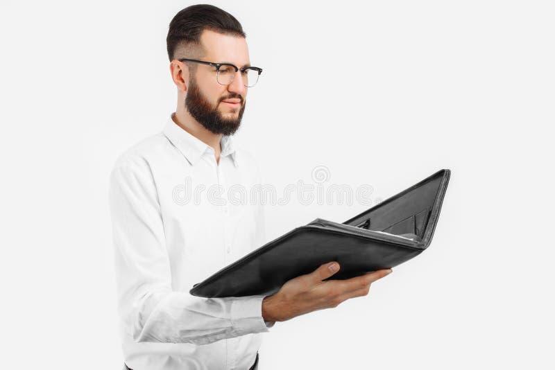 Man med en mapp i hans händer, på en vit bakgrund, affärsman med exponeringsglas royaltyfri bild