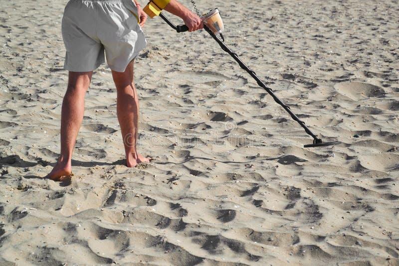 Man med en metalldetektor på en sandig strand för hav i sommardag royaltyfri fotografi