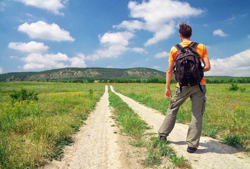 Man med en ryggsäck på en landsväg. Manturist. royaltyfri bild