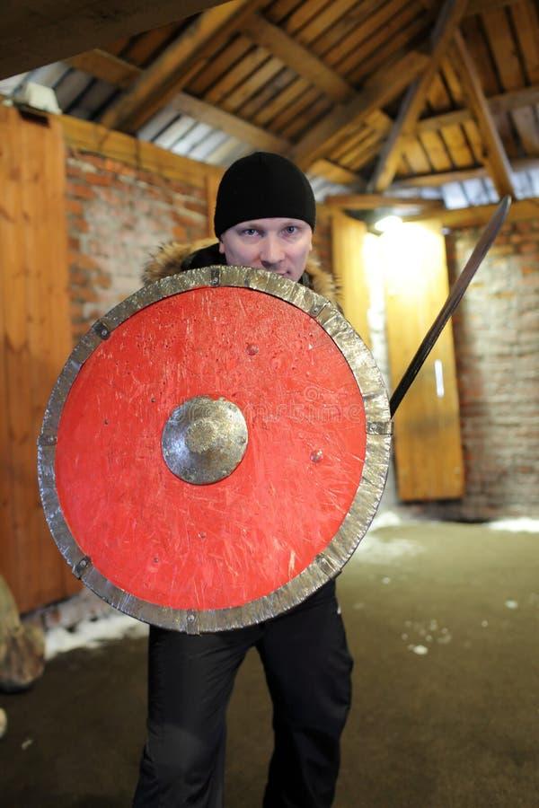 Man med en sköld och ett svärd arkivbild