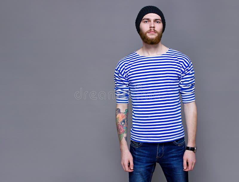 Man med en tatuering på hans hand, studio arkivbild