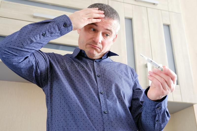 Man med en termometer i hans hand Ökande kroppstemperatur royaltyfri fotografi