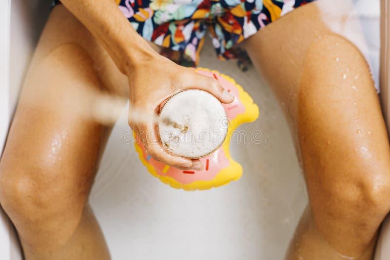 Man med ett exponeringsglas av öl i badkaret royaltyfri fotografi