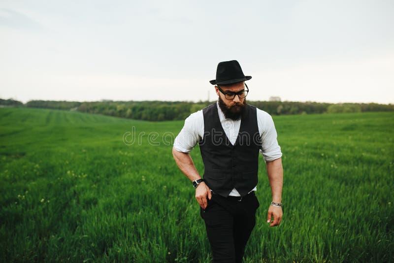 Man med ett skägg och solglasögon som går på fältet arkivfoton