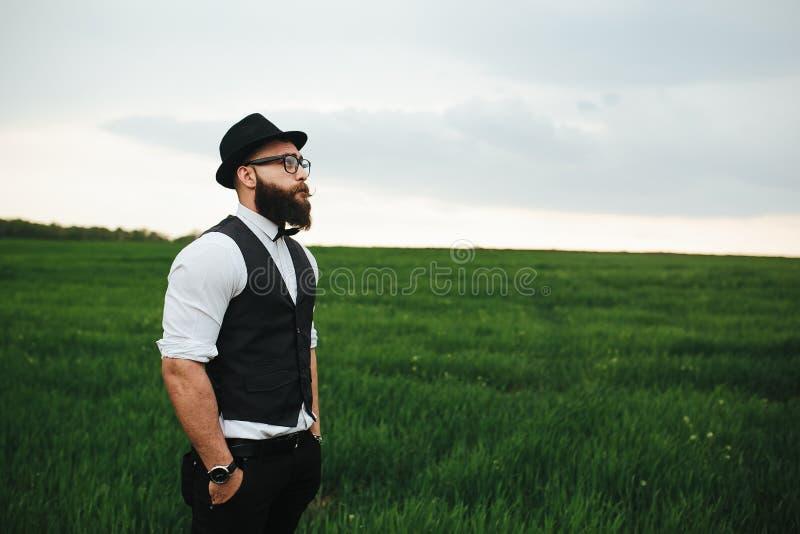 Man med ett skägg som går på fältet royaltyfri bild