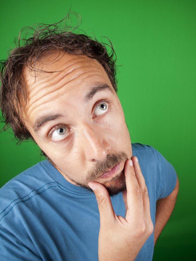 Man med ett skägg som slår hans haka medan i djupa tankar arkivfoto