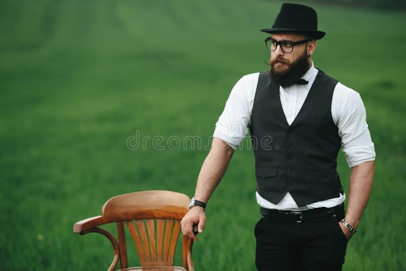 Man med ett skägg som tänker i den near stolen för fält arkivfoton
