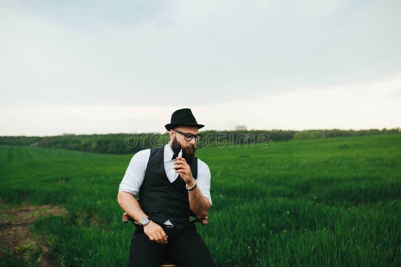 Man med ett skägg som tänker i fältet arkivfoton
