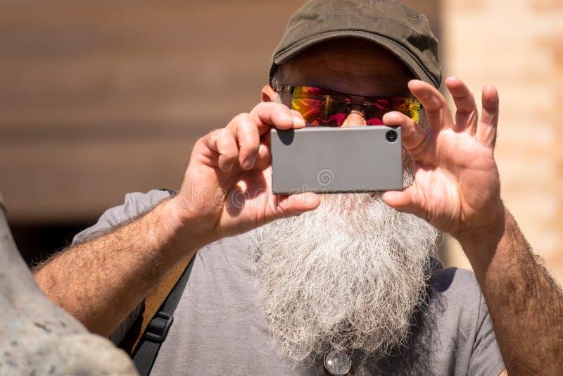 Man med ett skägg som tar ett fotografi med hans smarta telefon royaltyfri foto