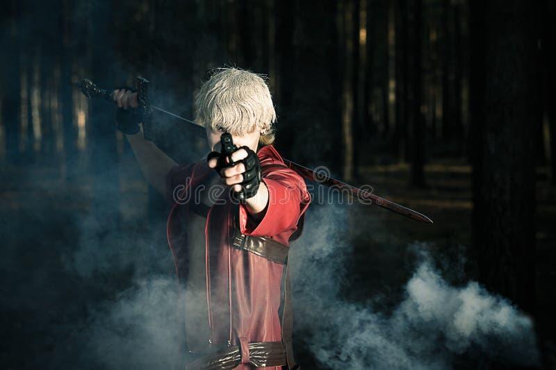 Man med ett svärd och ett vapen i händerna royaltyfri foto