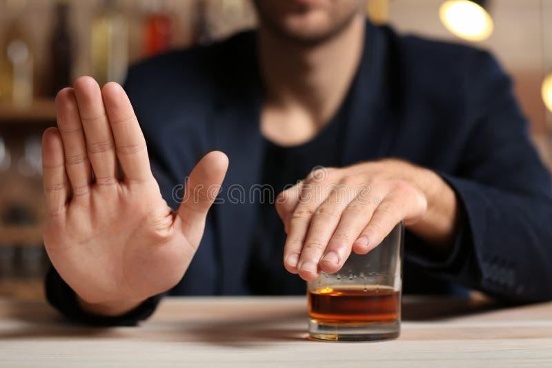 Man med exponeringsglas av whisky på tabellen som vägrar att dricka arkivbild