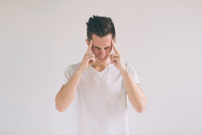 Man med exponeringsglas som har problem och huvudvärk hemma För t-skjorta för ung svart-haired nerdgrabb bärande vita händer inne royaltyfri fotografi