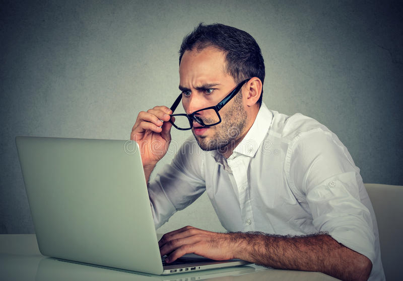 Man med exponeringsglas som har synförmågaproblem som är förvirrade med bärbar datorprogramvara royaltyfria foton