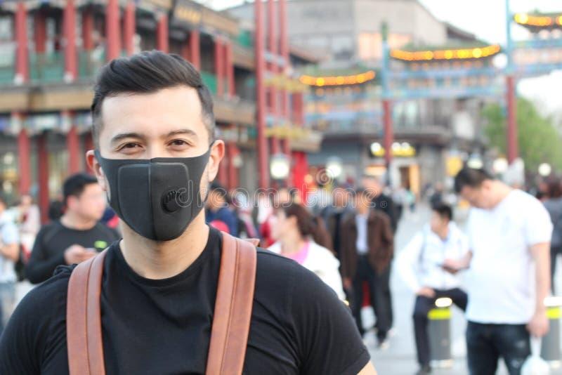Man med föroreningmaskeringen som står ut från folkmassan arkivfoto