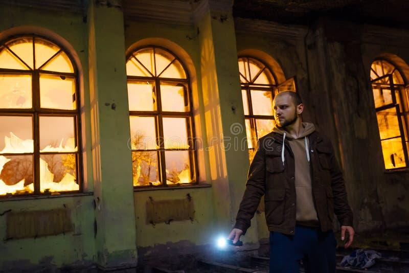 Man med ficklampan i mörk kuslig övergiven herrgård på natten royaltyfri foto
